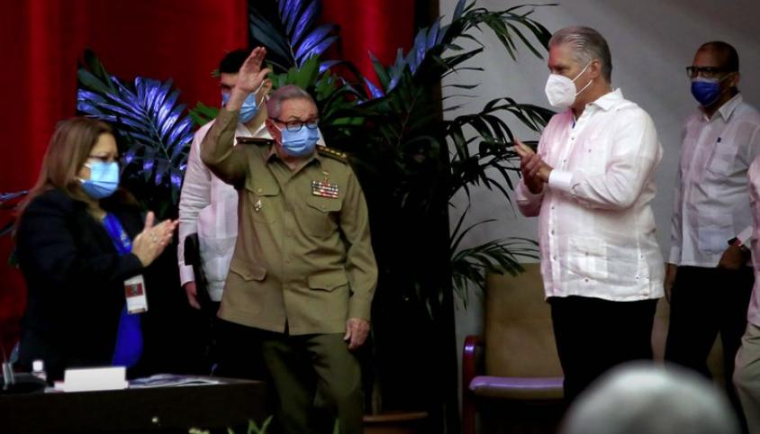Raúl Castro, primer secretario del Partido Comunista y expresidente de Cuba, saluda a los miembros en la sesión inaugural del VIII Congreso del Partido Comunista de Cuba, mientras el presidente cubano Miguel Díaz-Canel, derecha, aplaude en el Palacio de Convenciones, en La Habana, Cuba, el viernes 16 de abril de 2021. (Ariel Ley Royero/ACN vía AP)